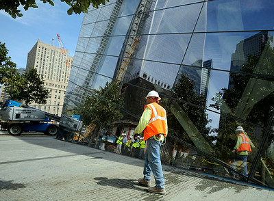A construction worker walks past the glass wall of a building at One World Trade Center in September 2011. (Photo by Jackie Schear)