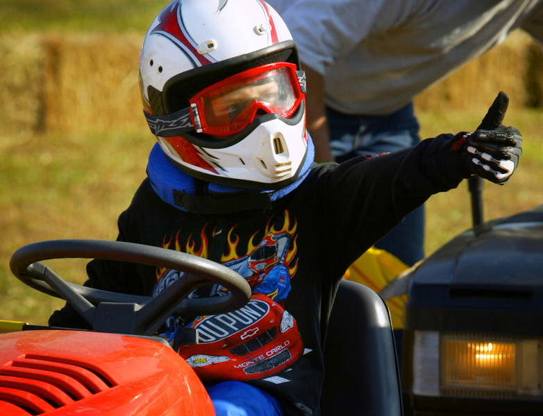 "Engine revving and safety gear in place, Tanner Clark signals his dad that all systems are ""go"" for a kid's stock race in Mt. Pleasant, Tennessee."