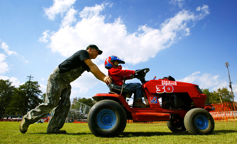 Dwarfed by his mower, Tanner Clark gets a push from his dad, Tracy, enroute to the starting grid before a race in Hohenwald, Tennessee.