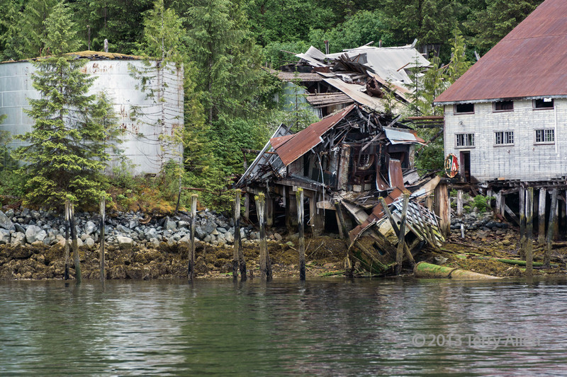 Remains of furnaces and old boat with cannery building and fuel tanks, Butedale, Princess Royal Island, British Columbia