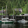 Sailboat moving past Butedale wharf, Butedale, Princess Royal Island, British Columbia
