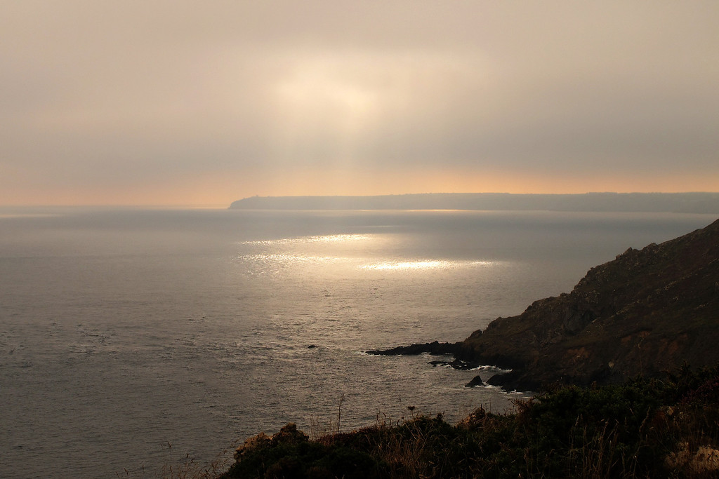 The sun searches for holes in the cloud.   Looking back to Lizard Point from Black Head.
