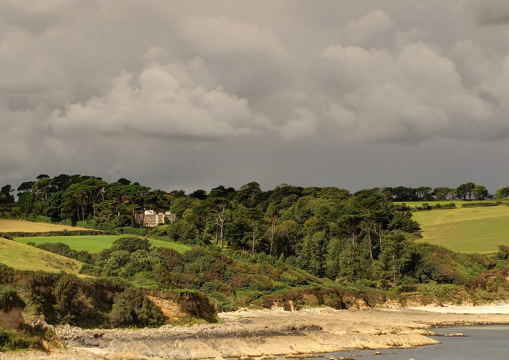 Round Rosemullion Head and the gardens of the Meuden Hotel come down to the beach at Bream Cove.   The hotel is not visible, hidden behind the trees.