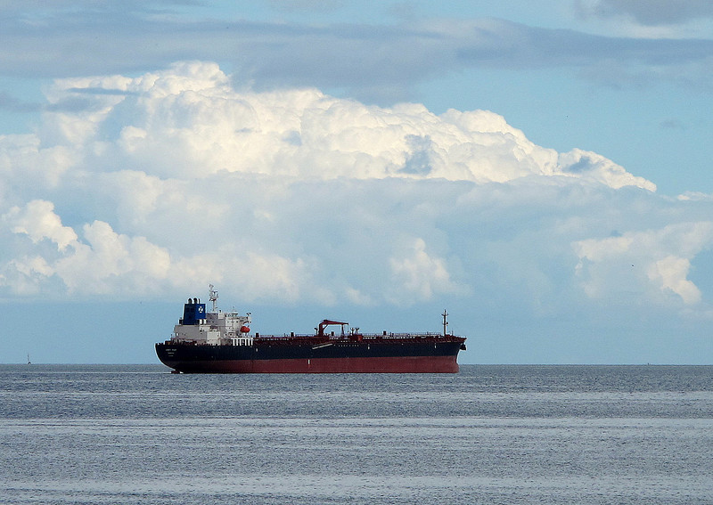 Another moored tanker stands offshore.
