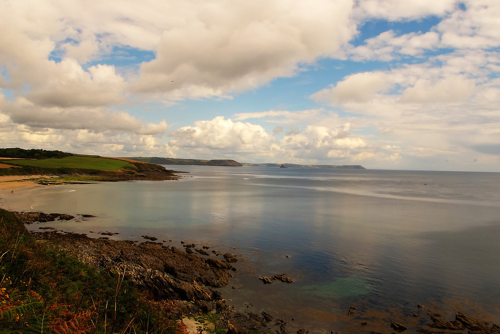 A serene sea.   The view from Killigerran Head across Towans Beach.   The headland in the mid distance is Nare Head with the far headland being Dodman Point.   Today's destination, Portloe, lies between theses two.