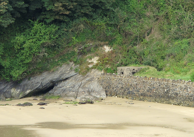 A Type 22 pillbox from the 2nd World War watches over the beach at Porthluney Cove in front of Caerhays Castle.