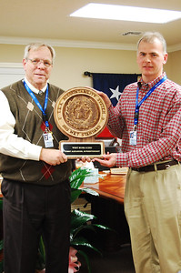 Superintendent Mr. Tommy Alexander  accepts plaque for the district.