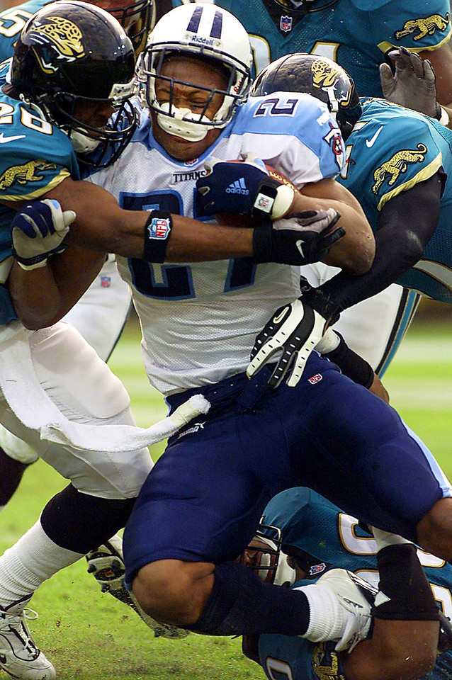 Tennessee Titans running back Eddie George, center, loses his helmet as he is crushed between Rayna Stewart, left, and Kevin Hardy of the Jacksonville Jaguars at the Coliseum in Nashville, TN.