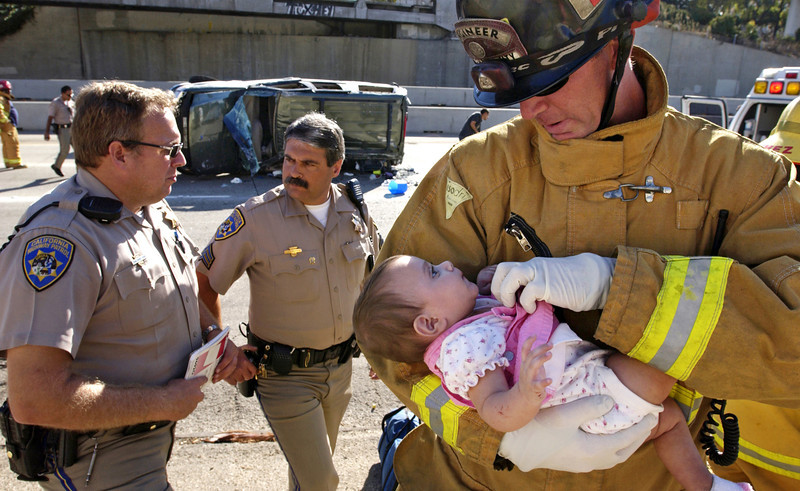 Ventura City Fire engineer Tom Hoffman, right, checks the condition of an unidentified child that was one of two infant passengers in an SUV that rolled over on northbound U.S. 101 at California St. in Ventura.   CHP officer Chris Terry, left, was the first highway patrolman on the scene and led the accident investigation with the help of CHP Sgt. Tony Viaropulos, center.  The victims of the crash received an outpouring of support from the public as a result of this photo appearing in the Ventura County Star, including cash donations as well as a replacement vehicle.  The wrecked SUV was the family's only vehicle.