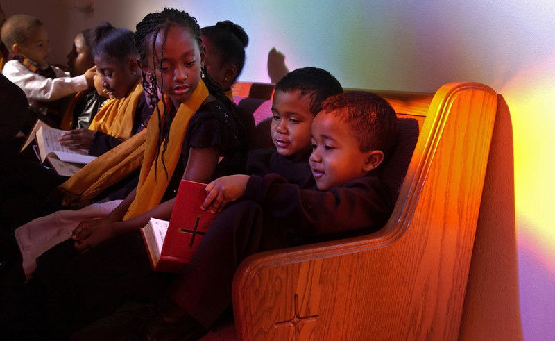 From left, Pastor's Choir members Danielle Dennis, 7, Amani Harkness, 5, and Xavier Harkenss, 4, look through a hymnal before the start of the Martin Luther King Jr. Celebration at Simi Second Missionary Baptist Church  in Simi Valley.