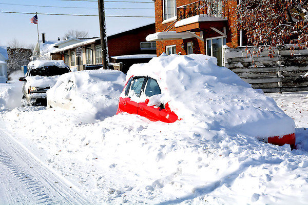 Vehicles were snowed and plowed in across Effingham on Monday as more than a foot of snow and high winds left a massive amount of snow in the city. These vehicles were on East Market Avenue.