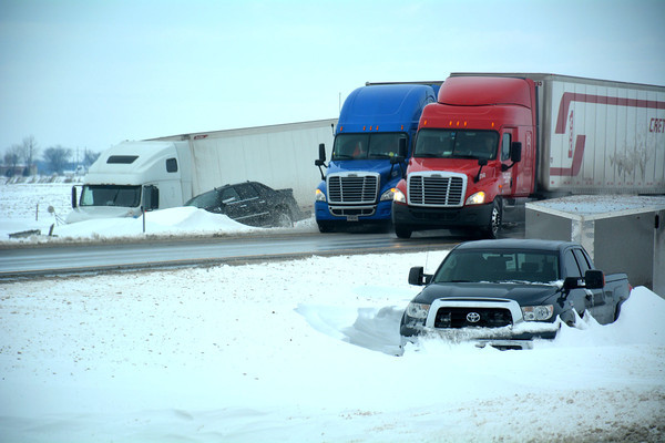 Several vehicles are in the ditch and still surrounded by around one foot of snow on Interstate 57.