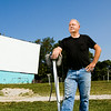 Owner Bill Powell, Georgetown, stands next to a pair of speakers in front of screen two at the Georgetown Drive-In. The theater has been run by Powell's family for 49 of the 63 seasons it has been in operation. Staff photo by Christopher Fryer