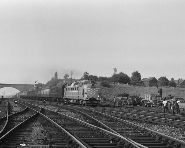 The prototype Deltic is seen approaching Knebworth in September 1959.  Of almost as much interest is the permanent way gang and the assorted vehicles parked in the adjacent yard.  The flat bottomed track in the right foreground is so new that the chalk markings are still visible.  Perhaps this has something to do with the presence of the permanent way gang.