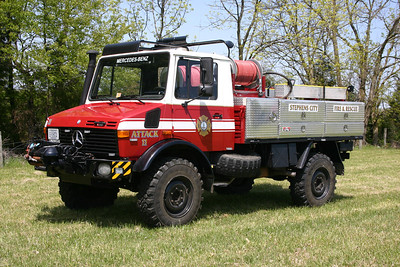 "In 2013, Stephens City placed into service a most unusual truck.  Attack 11 (re-designated as Brush 11 in 2016) is a 1985 Mercedes Benz Unimog 1300L.  The Unimog was donated to Station 11 by a local Frederick County family.  It was originally painted white and is an ex- German military truck.  It was purchased by the Frederick County family and then donated to Stephens City in 2012.    The brush skid unit from the departments 1985 Ford F brush truck was transferred to the Unimog.  In addition, LSI built the large box behind the cab and the fire department added the cabinets, completed the plumbing, and added the graphics.  One final item that makes this truck unusual - there is a large ""sunroof"" above the officers cab.  This was originally used for a military gun.  There is still a gun holder and ammunition box in the cab.  Photographed in April of 2013 at a fire department members home."