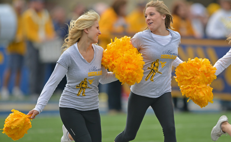 OCTOBER 19 - MORGANTOWN, WV: Members of the alumni cheerleaders run onto the field prior to the Big 12 football game October 19, 2013 in Morgantown, WV.