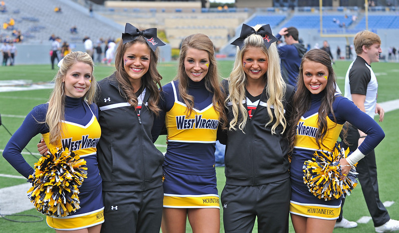 OCTOBER 19 - MORGANTOWN, WV: Members of the Texas Tech and WVU cheerleading squads pose for a photo prior to the Big 12 football game October 19, 2013 in Morgantown, WV.
