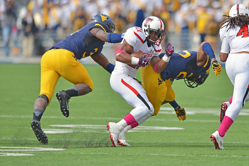 OCTOBER 19 - MORGANTOWN, WV: Texas Tech running back DeAndre Washington (21) runs over a defender on a carry during the Big 12 football game October 19, 2013 in Morgantown, WV.