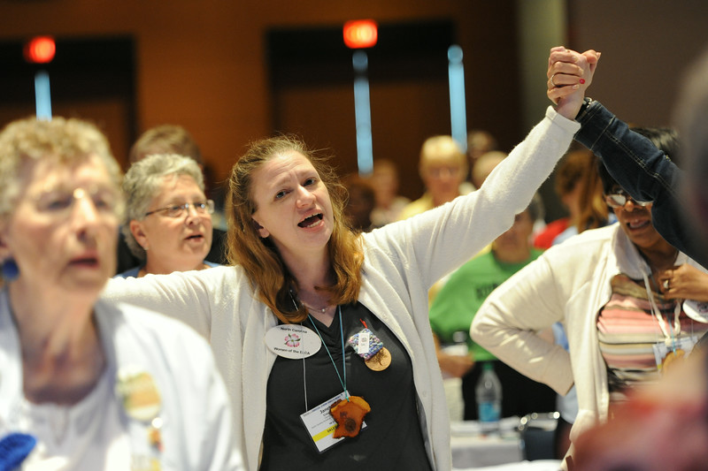 Ninth Triennial Convention | Janet Creasy, Liberty, NC sings with hands raised during a brief recess.