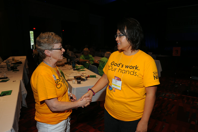 "Ninth Triennial Convention | Caitlin Vang, Milwaukee, WI and Linda Miranda, Chicago, IL in matching ""God's Work. Our hands"" shirts."