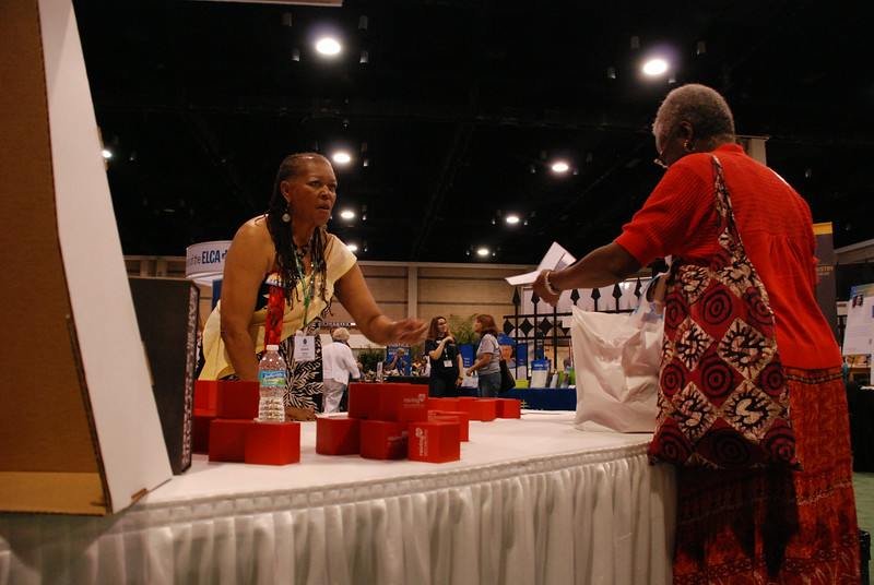 """Victoria Jackson, a pastor at St. John's Lutheran, Jacksonville, Fla. (left), talks with participants about the Women of the ELCA's """"Raising Up Healthy Women and Girls"""" initiative. Emblazoned with the name of the initiative, the red """"stress balls"""" are actually square. EH."""