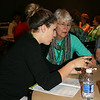 Ninth Triennial Gathering | Mariah Curtin (left) teaches another woman how to tweet during the Cafe group workshop
