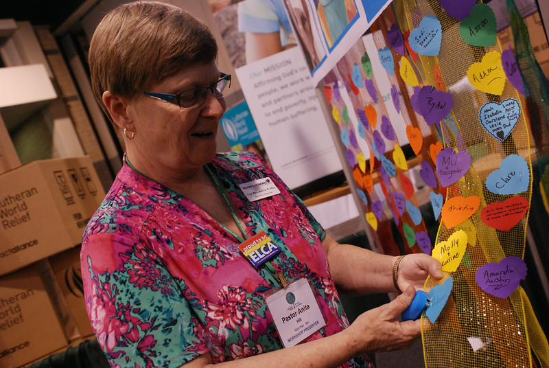 Pastor Anita Hill, regional director of Reconciling Works: Lutherans for Full Participation, tacks on more love for all of God's children at the Reconciling Works display. EH.