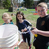 Mackenzie Orange, 7, Lucy Woodward, 7, and Joe Packard, 11, filled recycled bottles with colored water at the park on Memorial Drive in Ashburnham. Volunteers and local Girl Scouts gathered on Saturday to create a sculpture in memory of 6-year-old Kate Arpano who died from a rare brain cancer in January. SENTINEL & ENTERPRISE / Ashley Green