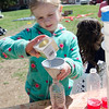 Mackenzie Orange, 7, dumps glitter into a colored bottle at the park on Memorial Drive in Ashburnham. Volunteers and local Girl Scouts gathered on Saturday to create a sculpture in memory of 6-year-old Kate Arpano who died from a rare brain cancer in January. SENTINEL & ENTERPRISE / Ashley Green