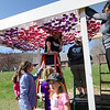 Volunteers hang recycled bottles filled with colored water onto a structure at the park on Memorial Drive in Ashburnham. Volunteers and local Girl Scouts gathered on Saturday to create a sculpture in memory of 6-year-old Kate Arpano who died from a rare brain cancer in January. SENTINEL & ENTERPRISE / Ashley Green