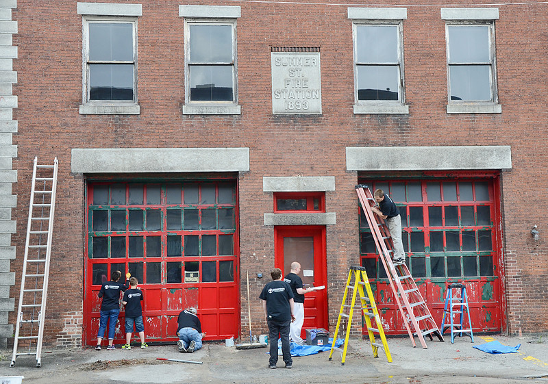 Approximately 350 volunteers from Crossroads Community Church spread out across Main Street on Saturday afternoon to revitalize the downtown area. Here, they touch up the paint at the old Summer St. Fire Station. SENTINEL & ENTERPRISE/ Ashley Green