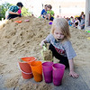 Rebecca Richter, 3, plays in the sand pile during the Civic Days Block Party on Saturday evening. SENTINEL & ENTERPRISE / Ashley Green