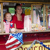 Addison Brooks, 8, and mom Audrey, from the Farm at Baptist Common in Templeton, sell popcorn during the Civic Days Block Party on Saturday evening. SENTINEL & ENTERPRISE / Ashley Green