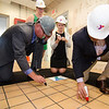State Representative Stephan Hay and Mayor Stephen DiNatale sign the floor during the official kickoff to the capital improvement rennovation project at the YMCA in Fitchburg on Wednesday morning. SENTINEL & ENTERPRISE / Ashley Green