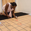 Leona Shaw signs the tile floor during the official kickoff to the capital improvement rennovation project at the YMCA in Fitchburg on Wednesday morning. SENTINEL & ENTERPRISE / Ashley Green