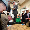 State and city officials along with guests sign a piece of the old tile floor during the official kickoff to the capital improvement rennovation project at the YMCA in Fitchburg on Wednesday morning. SENTINEL & ENTERPRISE / Ashley Green