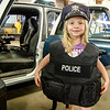 Molly Johnson, 6, tries on one of the Fitchburg Police Department vests during Fitchburg's annual DPW Day held on Wednesday. SENTINEL & ENTERPRISE / Ashley Green