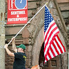 Mike Perry, of the Fitchburg DPW, hangs flags along Main Street on Friday morning in preparation for the July 4th holiday weekend. SENTINEL & ENTERPRISE / Ashley Green