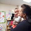 FRC program director Migdalia Velez hugs granddaughter Aria George at the opening of the MOC Family Resource Center on Summer Street on Friday. SENTINEL & ENTERPRISE / Ashley Green