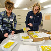 Jayne Matthews and Judy Griffin, volunteers from Workers Credit Union, label meal packages during the food packing event held at Simonds International on Thursday afternoon. Over 22,000 meals were packaged for local food pantries in partnership with the United Way of North Central Massachusetts. SENTINEL & ENTERPRISE / Ashley Green