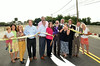 Guests and officials gather as Cheltenham Township Board of Commissioiners president Harvey Portner, center, cuts a ribbon to officially open the Greenwood Avenue bridge spanning the SEPTA tracks between Jenkintown and Cheltenham Township.   Monday, June 30, 2014.   Photo by Geoff Patton