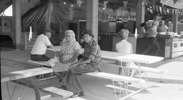 A couple rest on a picnic table bench under the grandstand during a fair in years gone by. Do you recognize them? If so, share the information under the photo online at the Effingham Daily News Facebook page.