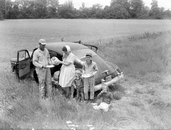 A family is on a picnic, or they have brought lunch to the field for dad in this photo from the newspaper archives. Do you recognize any of the people in the photo? If so, share the information below or on the Effingham Daily News Facebook page.