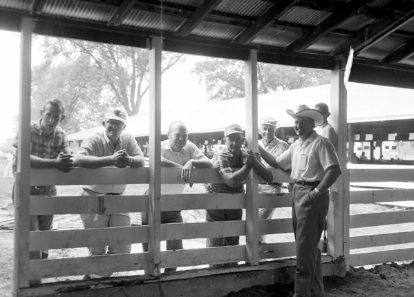 A group of men gather along the side of an exhibit building at the county fair. Do you recognize the men? Share the information online at the Effingham Daily News Facebook page.