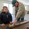 Mike Nutter, 4, smiles as Shaun LeFrancois helps him measure his fish during the Barrett Park fishing derby on Saturday morning in Leominster. SENTINEL & ENTERPRISE / Ashley Green