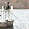 Michael Thao of Leominster fishes off the dock at Barrett Park on Monday morning. SENTINEL & ENTERPRISE/ JOHN LOVE