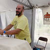 Ryan Daigle serves up a beer from the Gardner Ale House at the Johnny Appleseed Craft Beer Festival in downtown Leominster on Saturday afternoon. SENTINEL & ENTERPRISE / Ashley Green