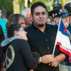 Transilvania Cespedes of Worcester clutches Mauricio Cardoza of Leominster, holding a Christian and American flag during during a Peace Vigil in Monument Sq. Leominster SENTINEL&ENTERRPRISE/ Jim Marabello
