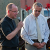 Leominster Mayor Dean Mazzarella looks on as Father Jose Rodriguez of Holy Family Trinity Church leads a prayer during a Peace Vigil in Monument Sq. SENTINEL&ENTERRPRISE/ Jim Marabello