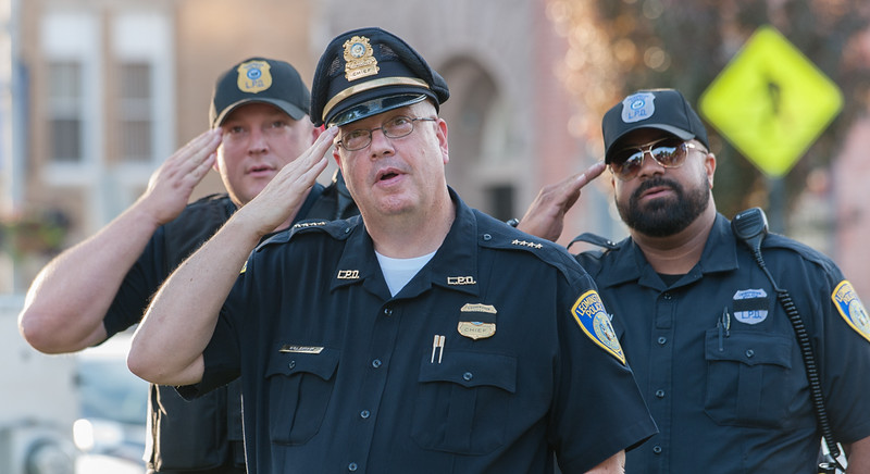 Interim Leominster Police Chief Michael Goldeman (lcenter), Sgt Johgn Fraher (left) and Ptl Carlos Cintron salute during the Pledge of Allegiance during a Peace Vigil in Monument Sq. SENTINEL&ENTERRPRISE/ Jim Marabello